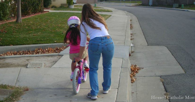 Setting a timer helps me to accomplish my goals. Image of a mom helping daughter ride a bike without training wheels.