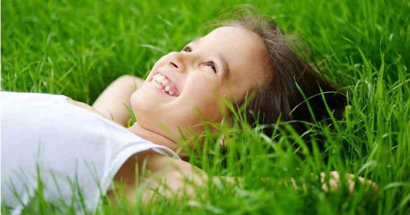 God places dreams in our hearts that are uniquely suited to us. We do not have to fear them. Dream big and work every day to make those dreams a reality. Image of a young girl laying on her back on the grass, smiling and looking up at the sky.