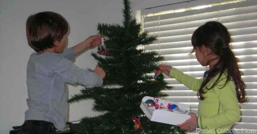 Celebrating Advent can be quite simple: we can chose to limit the secular focus of Christmas and spend some time spiritually preparing our hearts for Jesus. One way to do this is to leave your Christmas tree up until Epiphany. Image of two children decorating a Christmas tree. Blessed Catholic Mom logo on bottom.