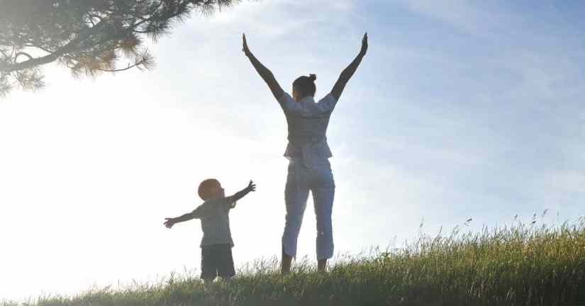 It can be challenging to live as God wants me to live on a daily basis. How do I know how God wants me to live each day? Ephesians, St. Paul tells us to live our vocation well. Image of woman and her son standing outside by a tree, facing the sun with their arms outstretched.