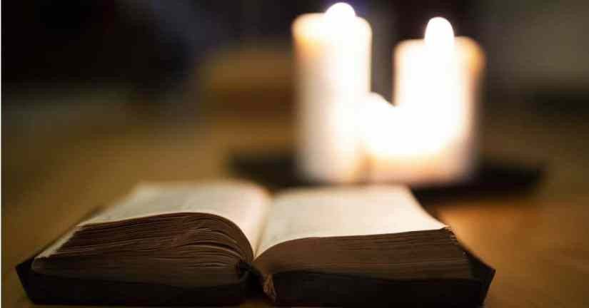 Spend time thinking about how to experience Lent beforehand. Make a plan that focuses on three different aspects: sacrifice, growth, and prayer. Image of an open Bible with three white candles lit behind it.