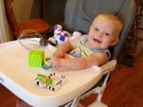 baby playing in Joovy high chair
