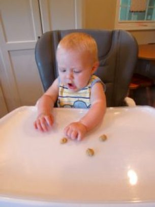 baby eating puffs in high chair