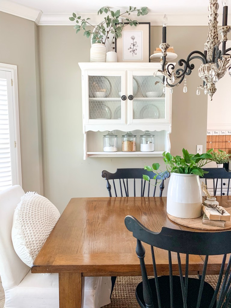 kitchen eating area with hanging hutch and farmhouse table
