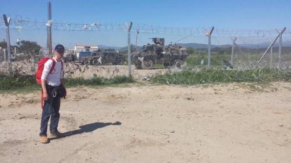 Vor dem mazedonischen Zaun mit Spendensachen auf dem Rücken