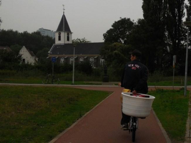 De fietser wil linksaf. In de achtergrond het standbeeld van de verdwenen boer en de verstopte boerin