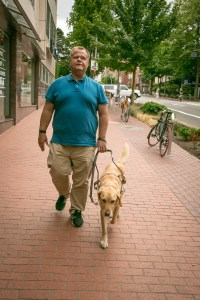 Nik and his guide dog are shown walking down the street outside of our downtown offices. Photo credit: Tristan Farzan