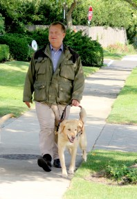 Miles Access Skills Senior Consultant Niklas Petersson walks with his guide dog on a neighborhood sidewalk.