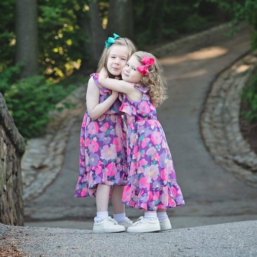 Nuala and Aoife in pink summer dresses hugging each other at a local park.