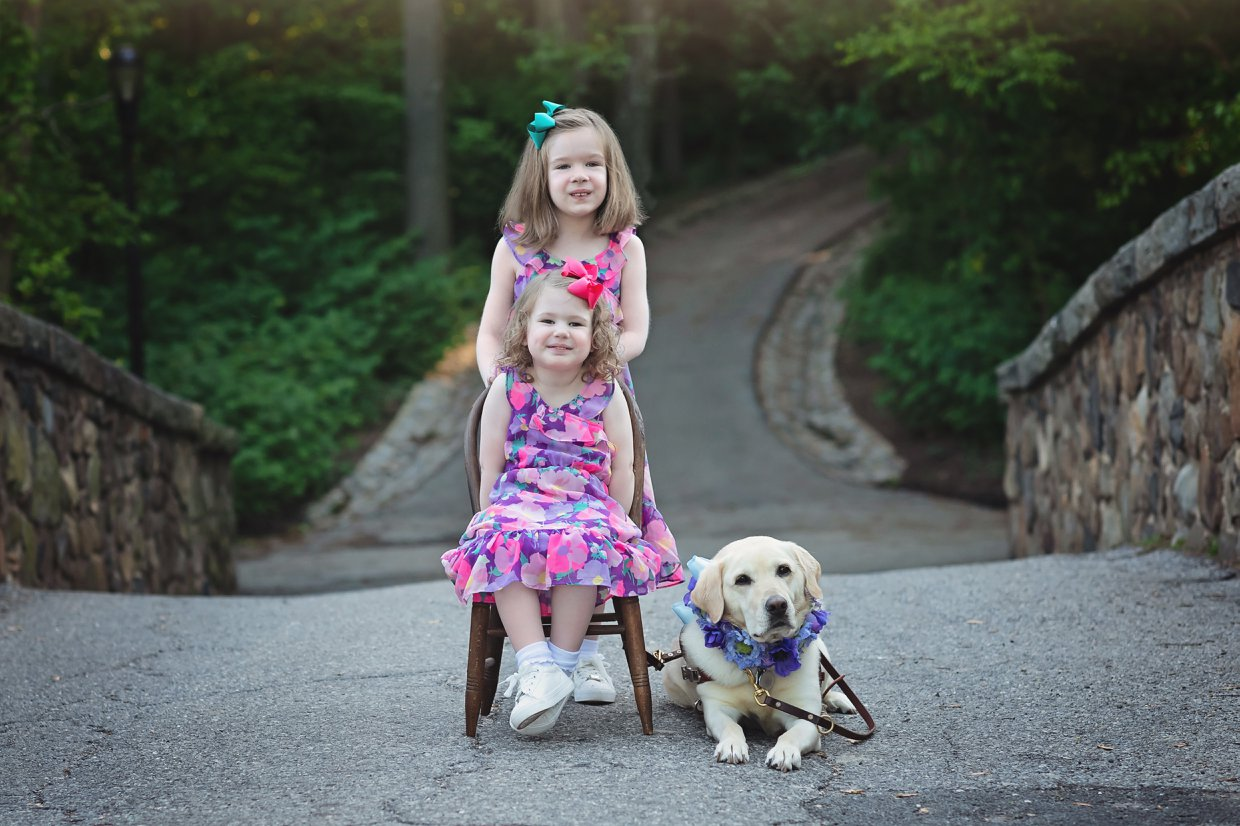 Nuala and Aoife in pink summer dresses with my guide dog, Frances. Aoife is sitting in a wooden chair, Nuala standing behind her. Frances is laying beside them wearing a collar adorned with blue and purple flowers.