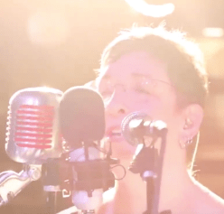 Image of Bekkah Hilgraves singing to three microphones during a recent recording session