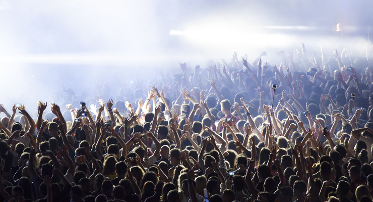 Large cheering crowd with their hands in the air at a concert