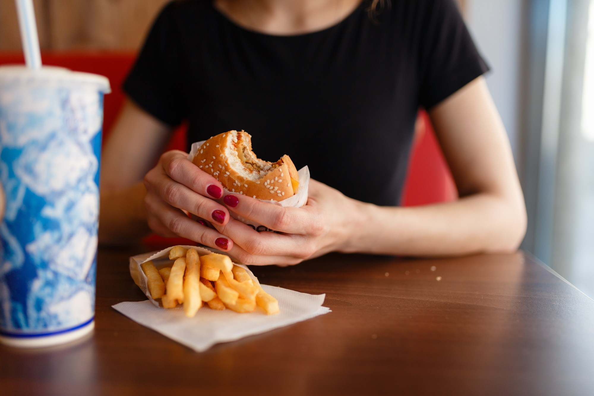 girl-holding-burger-and-fries