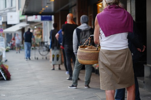 Low angle and selected focus, European people queue and wait for shopping on sidewalk outside supermarket
