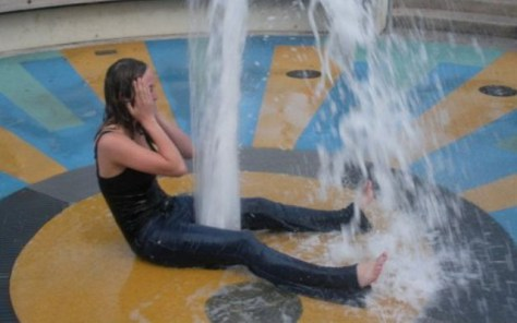 girl sitting over a gushing fountain that makes her look like she is squirting
