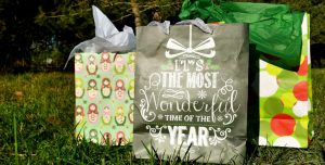 Image of gift bags with a backdrop of grass and evergreens.
