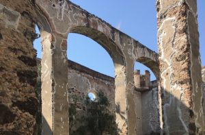 A picture of large stone arches of an old hacienda.