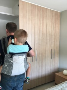 A picture of a man wearing an older child on his back in a carrier while house hunting.