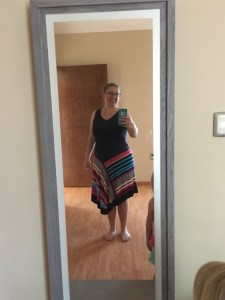 The blog author wearing a dress that is blue at the top and with different colored diagonal stripes on the skirt part.