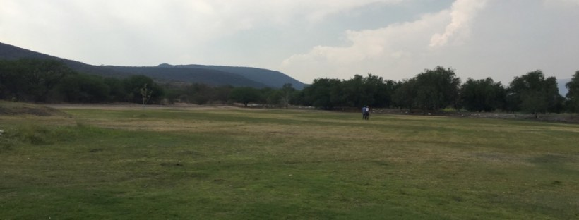 A mountain as a background and in the far distance, a child riding a donkey.