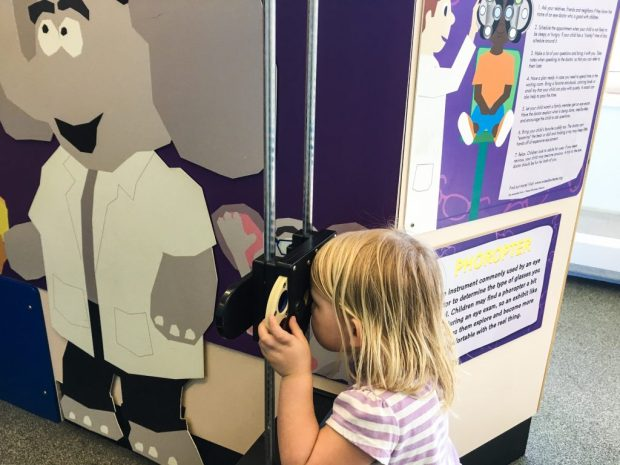 A blonde girl looking through child sized eye doctor eyesight checker thing.