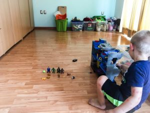 A young boy plays with batman toys.