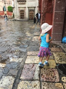 pictured: a litle girl in a hat wandering in the overcast, rainy area, surronded by old buildings and stone streets.