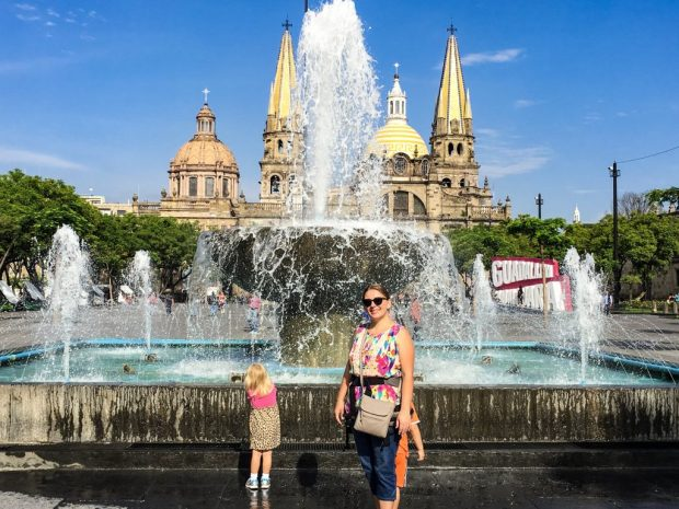 A woman, smiling in front of a fountain. One child hides behind her and the other has her back to the camera.