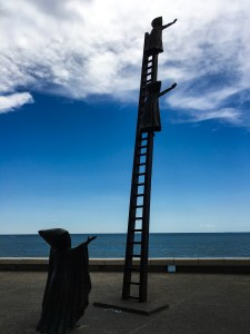 Statue: a person in a cloak reaching out, a ladder with two children in cloaks also reaching out towards the sea