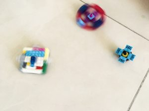 """three """"fidget spinners"""" made out of legos. Two are spinning. One of the unschool projects that I didn't force my child to make."""