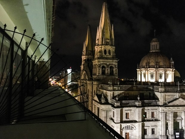 from a balcony, with ironwork at eye level on the left, and a beautiful church lit up on the left.