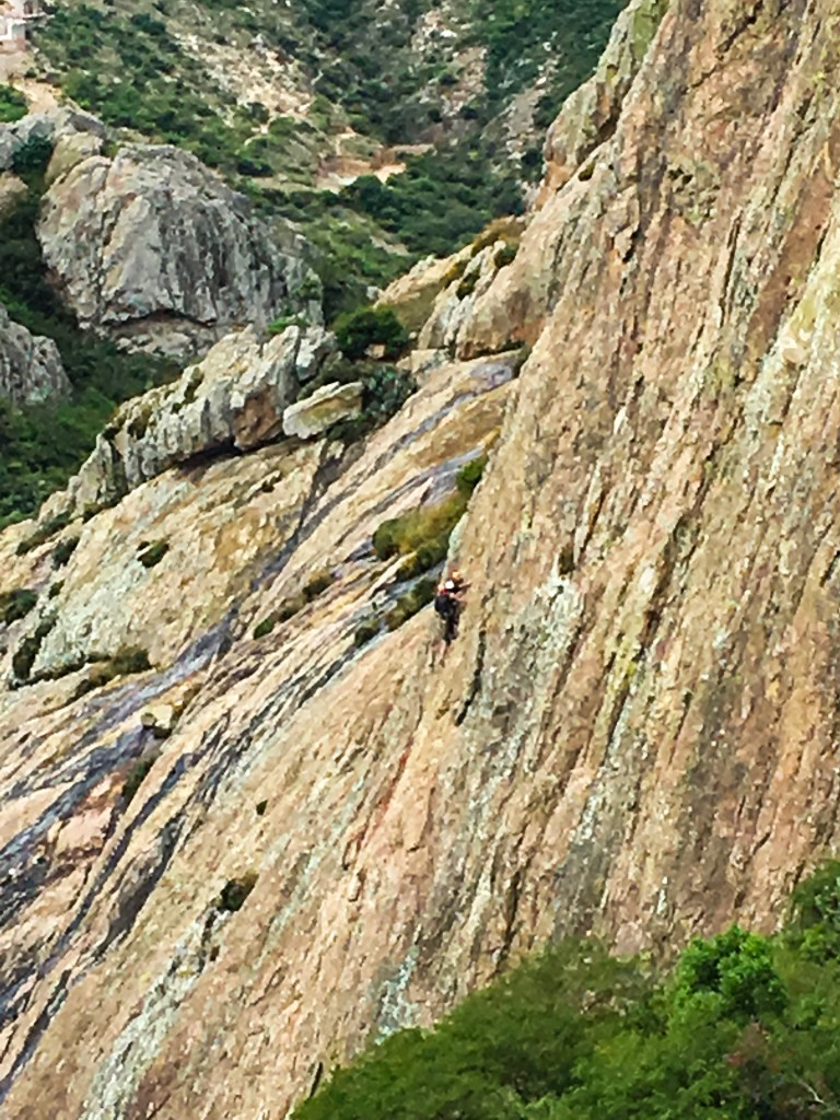 A picture of a sheer mountain face (the Pena de Bernal), with climbers (using gear).