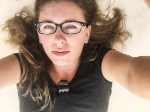 a picture of the author, wearing glasses and laying down on white tile. Her hair is light brown and a mess around her.