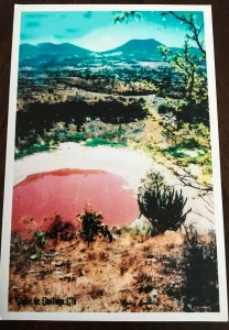 a picture of a postcard and on it is an old picture of when the crater was filled with water. In this picture, the water is a reddish pink color (likely caused by algae)