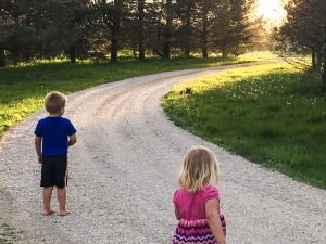 Two kids facing away from the camera on a stone driveway, as the sun sets in the background.