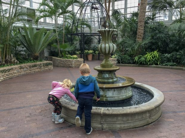 Two kids standing at a fountain, with greenery framing the outside of the picture. It evokes happy emotions for me!