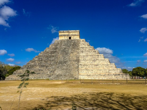 The famous pyramid of Chichen Itza. Three quarters of the pyramid is not restored and the remaining third is restored, showing up as a brighter, off white stone color.
