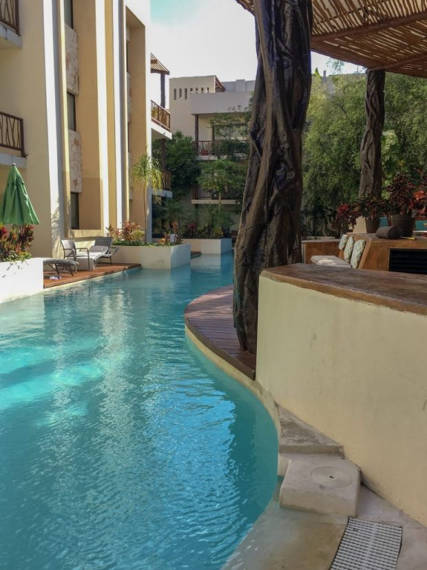 image is of a large, curved pool, surrounded by 3 story, white condo buildings. In the middle, there is a fake tree supporting a slatted roof over a seating area. The pool of our Tulum vacation!