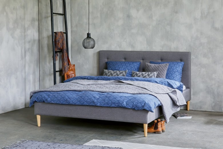 Grey bed with blue sheets and pillows
