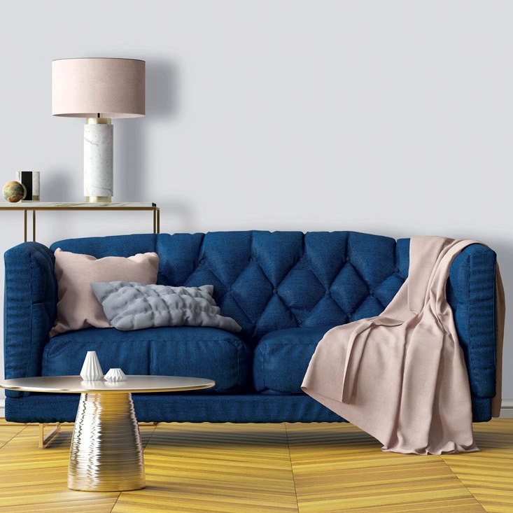 Rich blue sofa with a comforter on it