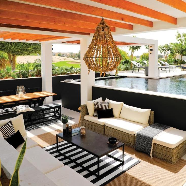 black and white sofas next to an outdoor pool
