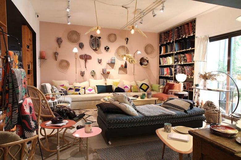 Inside Comptoir 102 in Dubai, cream sofa, navy chaise lounge, wicker chairs and wall hangings