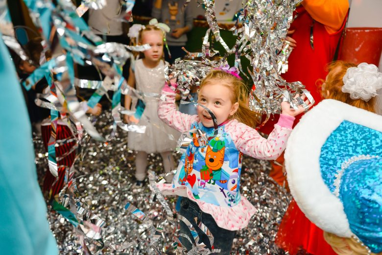 Little girl looks joyful jumping at party in tinsel confetti