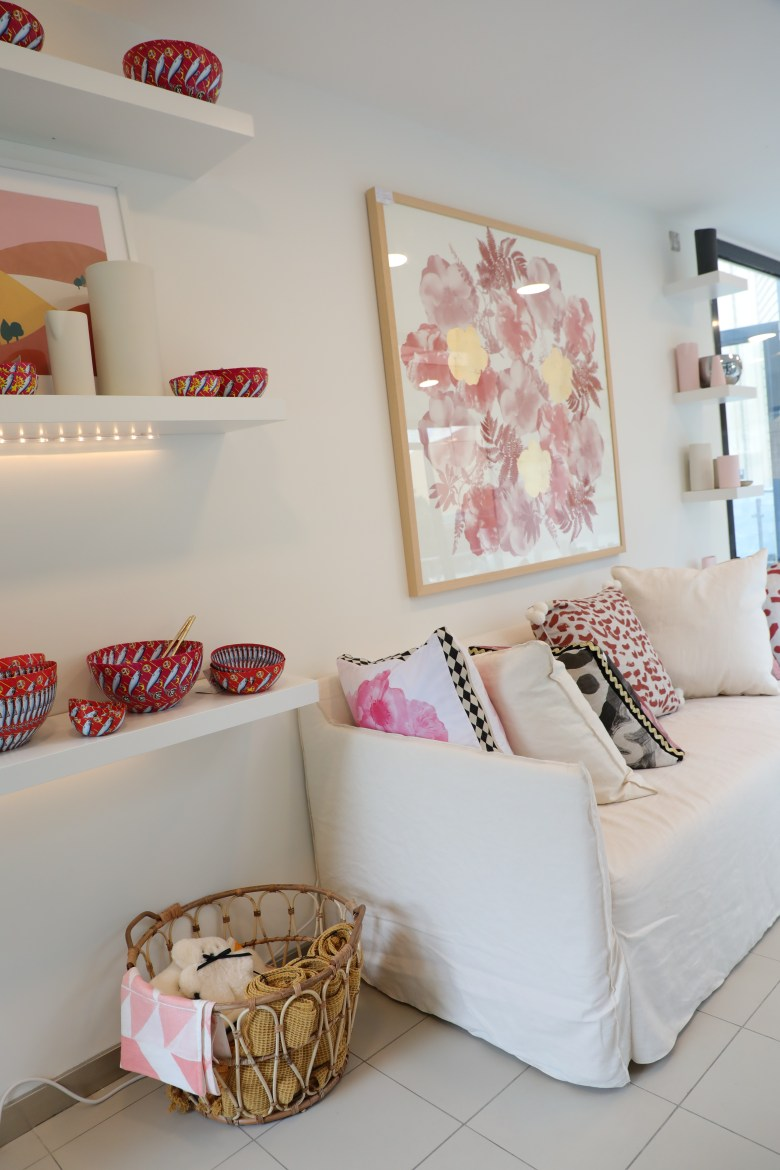 Georges of Dubai interior store cream sofa with pink cushions and red bowls on shelf