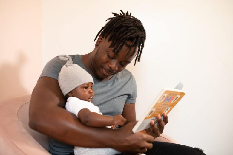 Man wearing grey shirt holds a baby in white and a grey hat and reads a picture book to him
