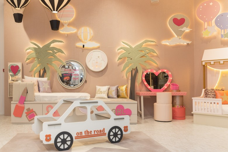 Kids bedroom with neon signs and pink walls