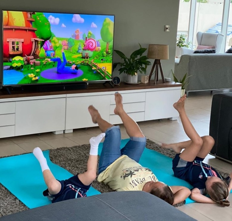 A family take part in an at-home PE lesson in their living room while distance learning in the UAE