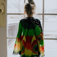 Little girl standing looking out of window in butterfly cape