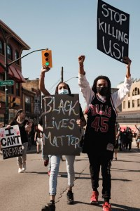 """Two Black people with raised fists in the air, holding signs; one reads """"Black Lives Matter"""" and the other says """"Stop Killing Us""""."""