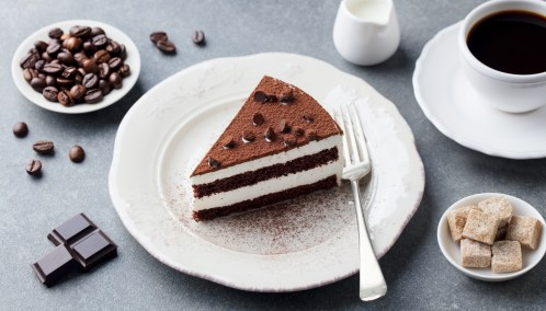 Tiramisu cake with chocolate decoration on a plate with cup of coffee. Grey stone background.